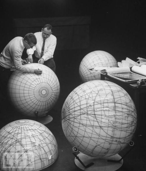 Scientists study the phases of the moon on lunar models in preparation for an eventual manned flight to moon