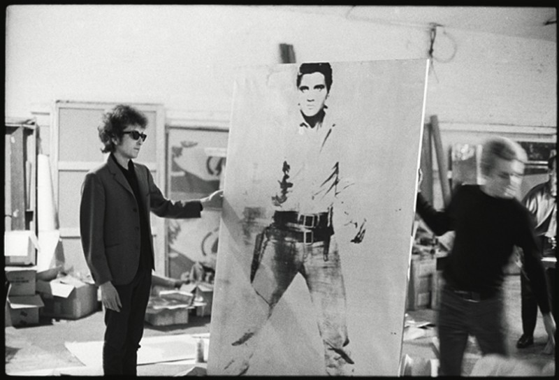 Bob Dylan with a Double Elvis screen print by Andy Warhol - The Silver Factory, 231 East 47th street New York, 1965 (photo Nat Finkelstein)