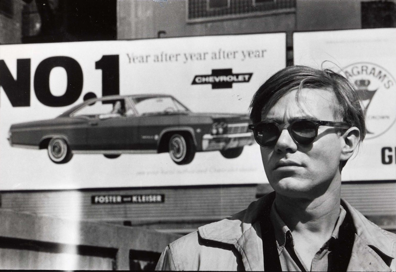 Andy Warhol, in front of a Chevrolet advertising