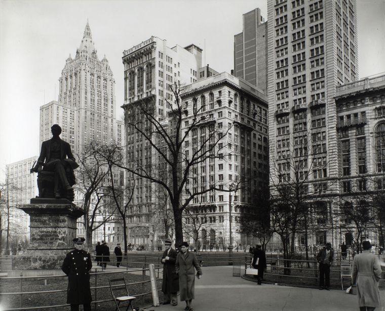 Berenice Abbott-Changing New York (1935-1938)-Madison Square, looking northeast, Manhattan, Policeman stands in front of Seward statue, shoe-shine man lounges on railing, right, Metropolitan Life building rises above park, March 20, 1936