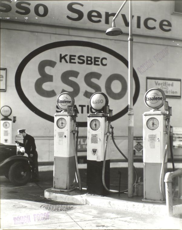 Berenice Abbott-Changing New York (1935-1938)-Man checks water in radiator of car left, bank of three pumps, right, at Kesbec Esso Station, Gasoline Station, Tenth Avenue and 29th Street, Manhattan, December 23, 1935