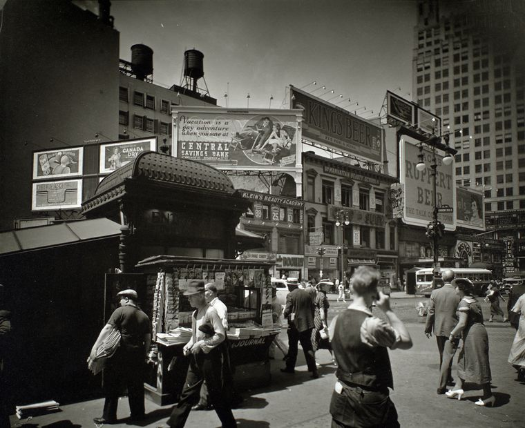 Berenice Abbott-Changing New York (1935-1938)-Union Square, 14th Street and Broadway, Manhattan, Men and women hurry past newstand outside uptown subway entrance, street beyond is lined with businesses topped with large billboards, July 16, 1936