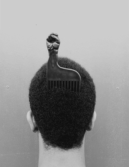 Man with a comb designed-like a raised fist, the -Black Power- symbol, in his hair