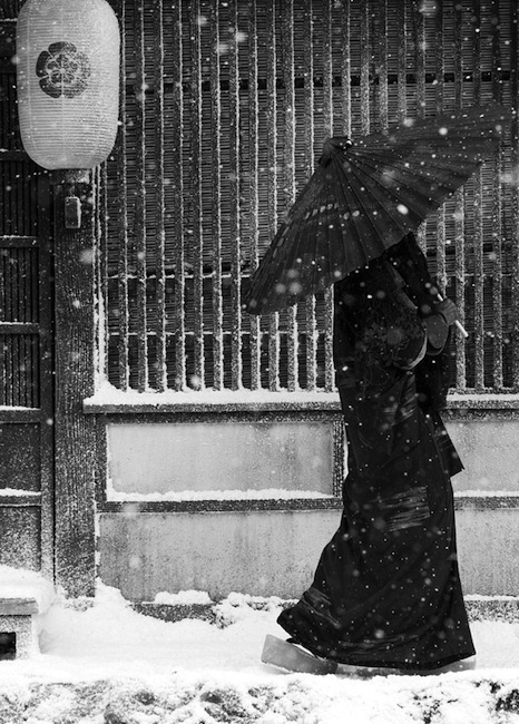 Japanese woman with an umbrella under falling snow