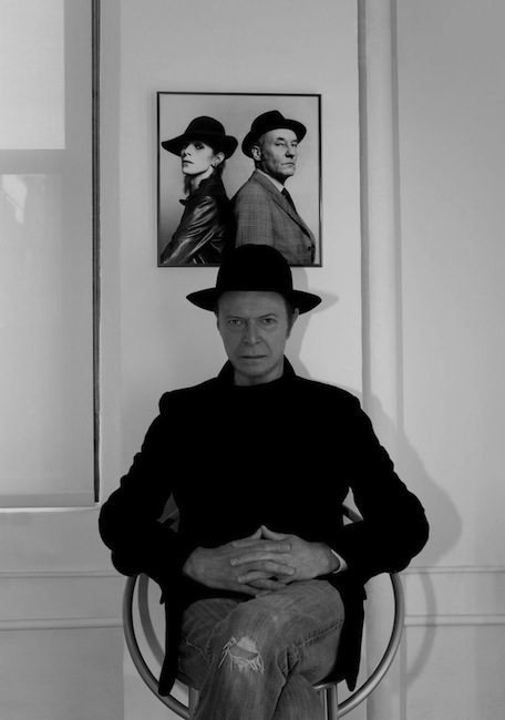 David Bowie sitting beneath a portrait of him, young, and William Burroughs, photo by Jimmy King, 2013